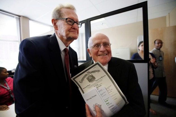 Jack Evans, 84, left, and George Harris, 82, right, show their marriage license after being the first couple to receive it from the Dallas County Clerk Friday, June 26, 2015, in Dallas. Evans and Harris, who have been together for 54 years were the first couple married after having their license issued. (AP Photo/Tony Gutierrez)