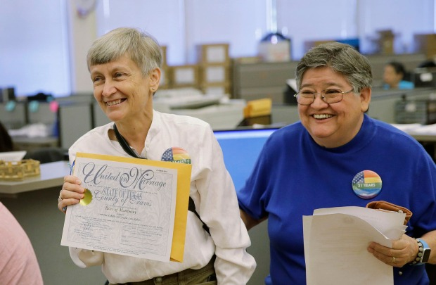 Jaque Roberts,  left, and her partner of 31 years, Carmelita Cabello, right,  show off their marriage license at the Travis County building after the U.S. Supreme Court ruled that  same-sex couples have the right to marry nationwide, Friday, June 26, 2015, in Austin, Texas. The court's 5-4 ruling means the remaining 14 states, in the South and Midwest, will have to stop enforcing their bans on same-sex marriage.(AP Photo/Eric Gay)