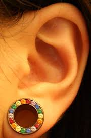 Ear stretching with coloured jewellery