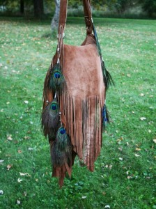 Fringed tan suede bag with peacock feather trim